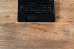 Portátil do computador na tabela de madeira do vintage do grunge Fotos de Stock