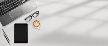 Portátil do espaço de trabalho do escritório, tabuleta, vidros do olho e café flatlay no desktop branco imagens de stock royalty free