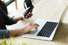 Portátil do uso da mulher e telefone esperto na mesa no lugar do escritório fotografia de stock royalty free