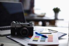 Portátil e câmera na mesa com dobrador foto de stock