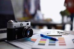 Portátil e câmera na mesa, dois empresários que estão no fundo fotos de stock