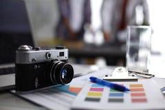 Portátil e câmera na mesa, dois empresários que estão no fundo fotos de stock royalty free