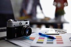Portátil e câmera na mesa no escritório, pessoa que está no fundo foto de stock royalty free