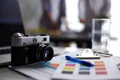 Portátil e câmera na mesa no escritório, pessoa que está no fundo imagens de stock royalty free