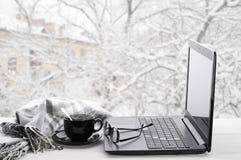Portátil e café na janela do inverno Imagens de Stock