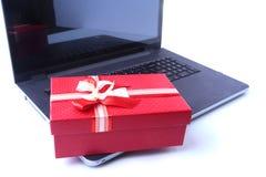 Portátil e caixa de presentes do Natal na mesa branca foto de stock