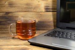 Portátil e copo do chá na tabela de madeira fotos de stock