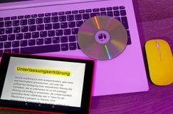Portátil e tabuleta em que um texto com uma declaração da omissão é indicado com o rato amarelo no sistema ótico violeta imagens de stock