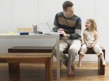 Portátil e telemóvel de And Daughter With do pai fotografia de stock royalty free