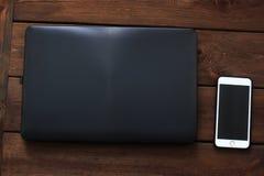 Portátil e telefone no fundo de madeira imagens de stock