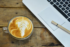 Portátil e uma chávena de café Fotos de Stock