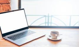 Portátil e xícara de café abertos na tabela no café, trocista acima, conceito autônomo imagem de stock
