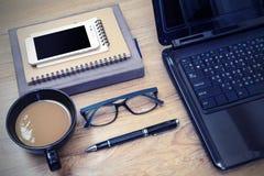 Portátil e xícara de café com a flor na mesa Fotos de Stock