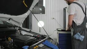 Portátil, equipamento moderno para a máquina dos sistemas de diagnósticos na estação do serviço, mecânico que trabalha na oficina vídeos de arquivo