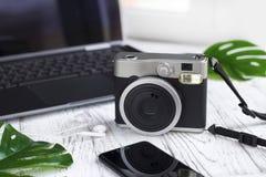 Portátil, folhas, câmera retro, telefone celular no branco Foto de Stock