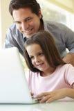 Portátil latino-americano de And Daughter Using do pai Fotografia de Stock Royalty Free