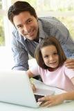 Portátil latino-americano de And Daughter Using do pai Imagem de Stock Royalty Free