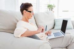 Portátil levando da mulher ao descansar no sofá imagens de stock royalty free