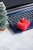 Portátil, pouca árvore de Natal e caixa de presente vermelha Foto de Stock Royalty Free