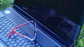 Portátil que encontra-se na grama no parque - estabeleça vidros no portátil video estoque