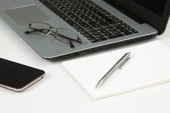 Portátil, telefone, bloco de notas, pena, vidros Imagem de Stock