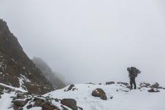 Portée de touristes le dessus d'une montagne neigeuse un jour d'hiver Photographie stock libre de droits