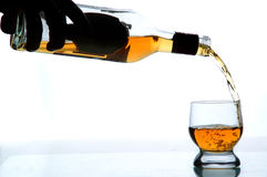Port. Someone pouring out alcohol into the glass, white background Royalty Free Stock Images