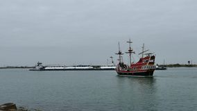 PORT ARANSAS, TX - 6 FEB 2015: Tourist excursion boat and commercial barge pass by each other. PORT ARANSAS, TX - 6 FEB 2015: Tourist excursion boat and stock footage