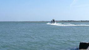 Port Aransas, TX - 6 MAR 2016: Jetty boat with tourists and fishermen leaves marina entrance. Port Aransas, TX - 6 MAR 2016: Jetty boat with tourists and stock footage