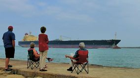 Port Aransas, TX - March 1, 2017: Seniors watch pilot boat along ship that is leaving Texas for Gulf of Mexico.