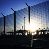 Port area fence with silhouettes of cranes Stock Photos