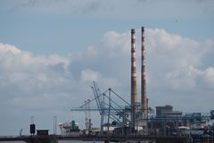 Port area and twin chimneys of Poolbeg Power Station, Dublin, Ireland. Skyline view along the River Liffey in Dublin Ireland towards the twin chimneys of Stock Image