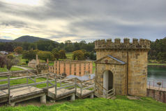 Port Arthur Watchtower. A stone watchtower on a green hill overlooking the historic Port Arthur penal colony, as the sun goes down. Port Arthur prison, Tasman Stock Image