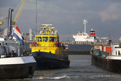 Port authority boat. Surrounded by ships in the Port of Rotterdam. Harbor traffic jam stock images