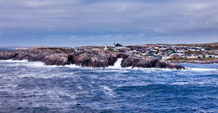 Port-aux-Basques NL town in Atlantic Canada. Port-aux-Basques village on Newfoundland, Atlantic Canada, with storm battered barren rocky shore protecting the royalty free stock photos