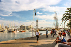 Port of Barcelona ambiance. Tourists and local people take sun, do some shopping and go restaurant in port of Barcelona Stock Image