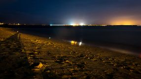 A port and beach at night with lights and star rays stock photography