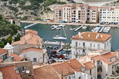 Port of Bonifacio, Corsica. A sailing boat enters the tranquil waters of the port of Bonifacio Royalty Free Stock Photos