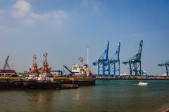The port of Bruges, Flanders, Belgium. A part of the port of Bruges with container cranes and tugs waiting for work Royalty Free Stock Images