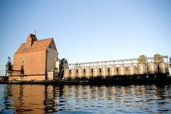 Port buildings. A huge brick building standing on a bank of a river leading to the sea. A row of storage facilities. Darlowo, Poland. The Wieprza river Royalty Free Stock Photo