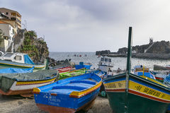 Port in Camara de Lobos. Boats on the shore of the ocean in the port near the Funchal in small fishing village Camara de Lobos on south coast of Madeira island Royalty Free Stock Images