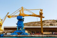 Port cargo crane in Shipyards harbor of Malta. In clear weather on a background of blue sky Royalty Free Stock Photography
