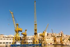 Port cargo crane in Shipyards harbor of Malta. In clear weather on a background of blue sky Stock Photography
