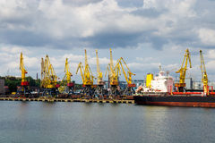 Port cargo cranes over the cloudy sky background Royalty Free Stock Photos