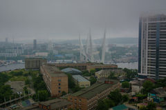 Port city view from the heights, high Bay braced bridge, thick fog. Marine City. Vladivostok royalty free stock photo
