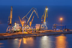 Port commercial de mer la nuit dans Mariupol, Ukraine Vue industrielle Le bateau de fret de cargaison avec le travail tend le cou Image stock