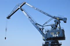 Port crane. Single blue port crane working Stock Photos