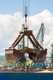 Port crane with scoop loading ship with wheat Stock Image