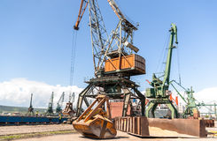 Port crane with scoop loading ship with wheat Royalty Free Stock Photography