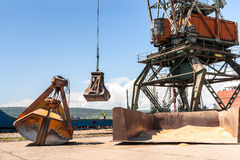 Port crane with scoop loading ship with wheat Royalty Free Stock Photo
